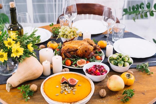Mesa festiva con pollo al horno y verduras.