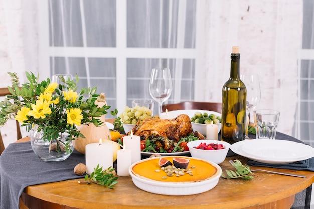 Mesa festiva con pollo al horno y vino.