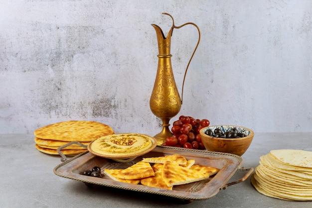 Mesa de fiesta india con hummus, pan y jarra de cobre