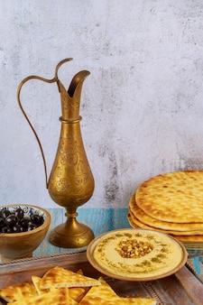 Mesa de fiesta judía con hummus, pan y jarra de cobre