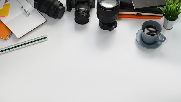 Mesa de fotógrafo con lente camerand, camerbag, computadora portátil y papel de cuaderno.