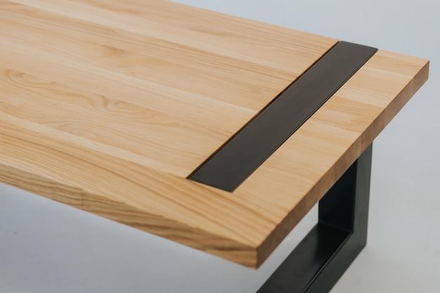 Mesa futurista hecha de una superficie de madera y metal negro.