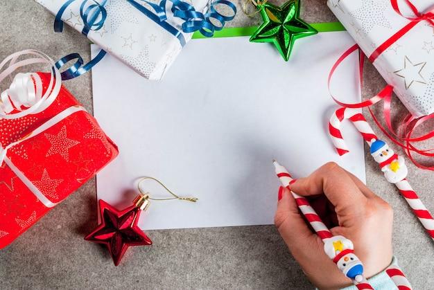 Una mesa gris con una hoja de felicitación, adornos navideños, una taza de chocolate caliente y un bolígrafo en forma de bastón de caramelo. niña escribiendo, mano femenina en la imagen, vista superior