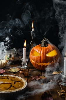 Mesa de halloween con jack o linterna, telaraña, velas y humo