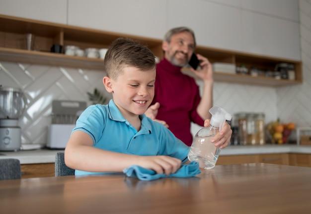 Mesa de limpieza de niño sonriente de tiro medio