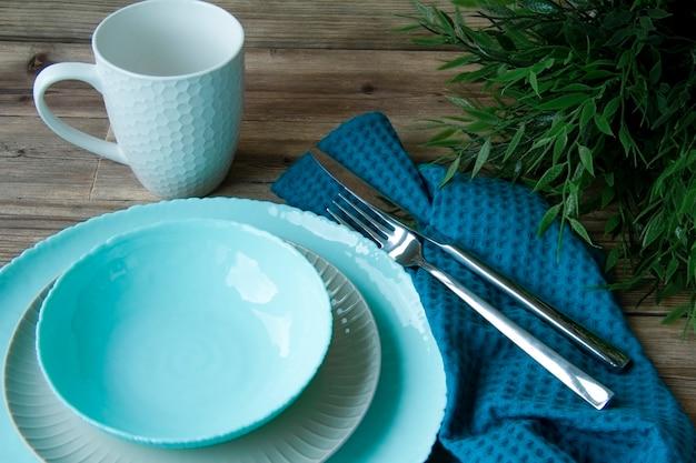 En una mesa llena de platos, una taza y cubiertos