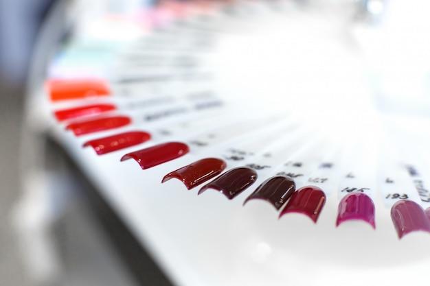 Mesa llena de utensilios de manicura, herramientas de manicura, colores de esmalte de uñas en la paleta. uñas accesorios de arte