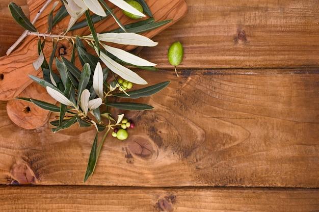 Mesa de madera con aceitunas y hojas.