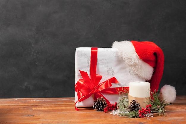 La mesa de madera con adornos navideños y caja de regalo.