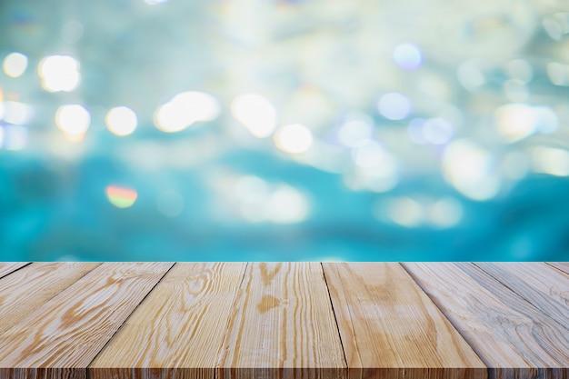 Mesa de madera con agua borrosa bokeh.