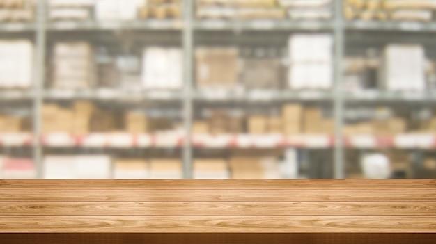 Mesa de madera en el almacén de almacenamiento borroso con copia espacio vacío en la mesa para la exhibición del producto.