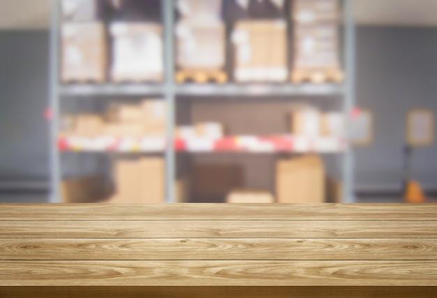 Mesa de madera en el almacenamiento del almacén fondo borroso con copia espacio vacío en la mesa para la exhibición del producto.