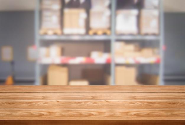 Mesa de madera en el almacenamiento del almacén fondo borroso con espacio de copia vacío en la mesa para la exhibición del producto.