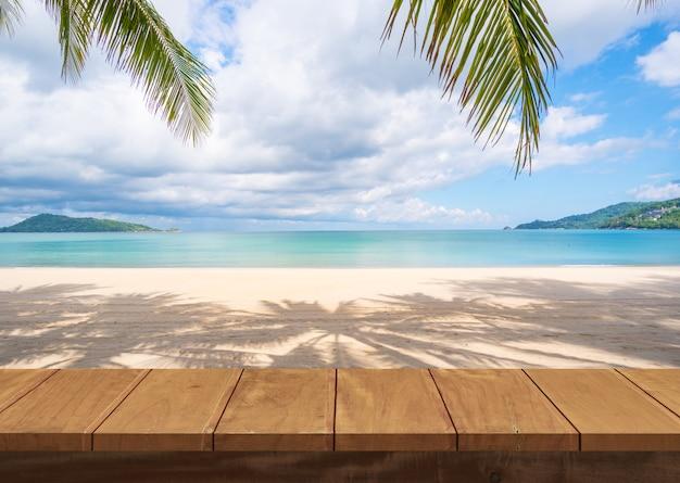 Mesa de madera y arena de mar de playa y palmeras en verano