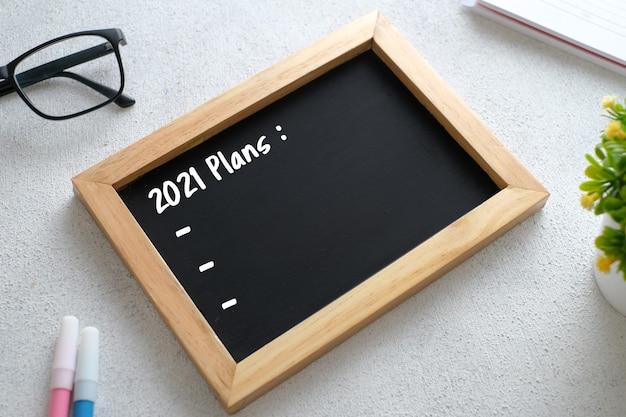 Mesa de madera blanca con anteojos, bolígrafo, plantas decorativas y pizarra escrita con la acción del plan de objetivos 2021. vista superior con espacio de copia, endecha plana.