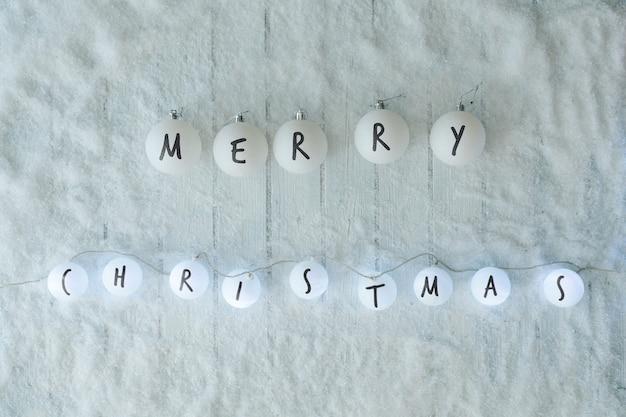 Mesa de madera blanca con decoración de bolas de nieve y luces. vista superior de invierno feliz navidad. colocación plana mínima.