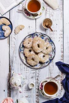 Una mesa de madera blanca con dos tazas de té y algunos pasteles.