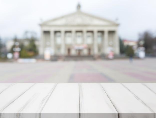 Mesa de madera blanca frente a fachada de edificio público clásico borrosa