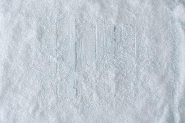 Mesa de madera blanca con nieve. vista superior de invierno o navidad. colocación plana mínima.