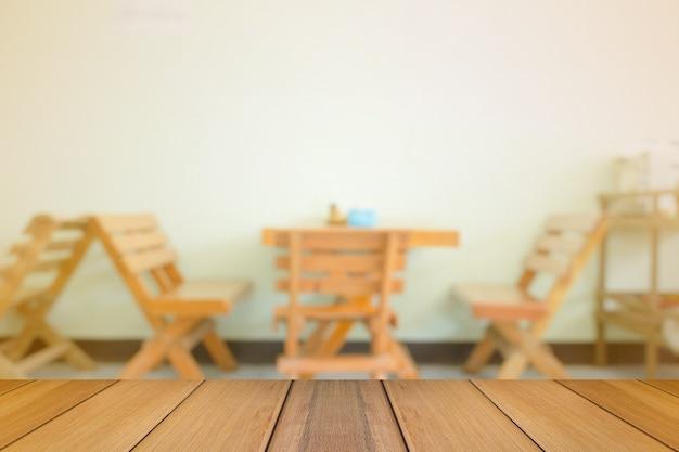 Mesa de madera en borrosa de comedor con luz cálida.