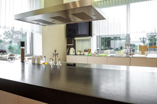 Mesa de madera y campana extractora sobre fondo borroso del interior de la cocina