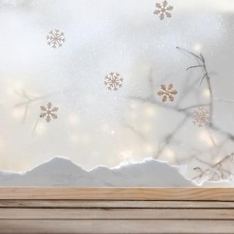 Mesa de madera cerca de banco de nieve, copos de nieve y luces de colores