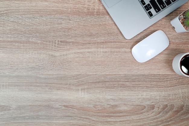 Mesa de madera con computadora portátil y taza de café negro