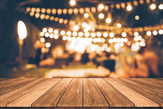 Mesa de madera delante del restaurante abstracto borrosa luces de fondo