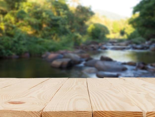 Mesa de madera delante de la vista borrosa abstracta del fondo natural begetation
