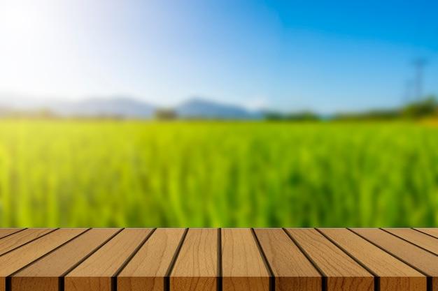 Mesa de madera y desenfoque de belleza en un día soleado en el campo de arroz con cielo y montañas como fondo.