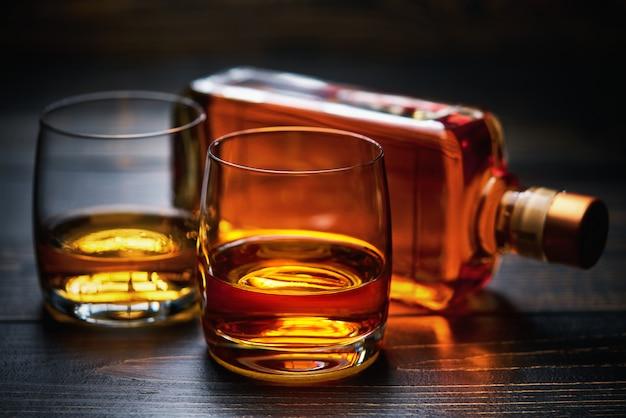 Mesa de madera con dos tragos de whisky y botella llena.