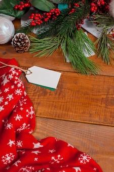 Mesa de madera con una etiqueta de precio en blanco vacía y adornos navideños.