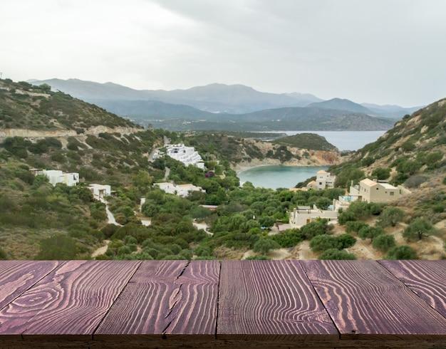 Mesa de madera exterior con vista a la montaña en un hermoso día de verano.
