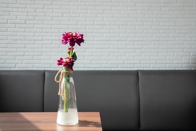 Mesa de madera con flor de zinnia en jarrón de vidrio.
