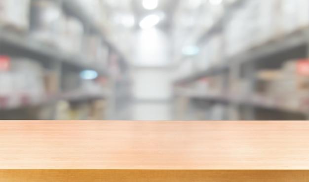 Mesa de madera en el fondo de desenfoque de almacenamiento de almacén con espacio de copia vacío en la mesa para la exhibición del producto
