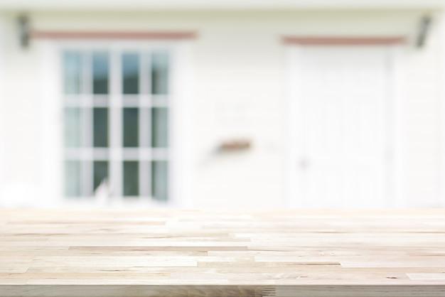 Mesa de madera en el frente de la casa blanca borrosa con puerta y ventana de vidrio
