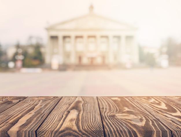 Mesa de madera frente a fachada borrosa de un edificio público clásico