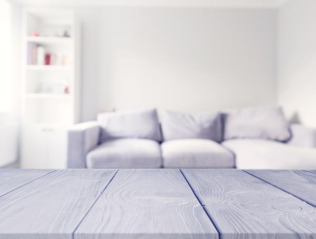 Mesa de madera gris frente a sofá blanco borroso en la sala de estar