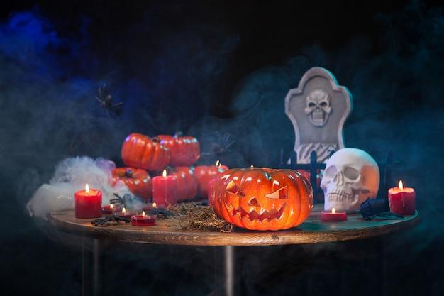 Mesa de madera con humo y decoración de halloween. calabaza tallada espeluznante para fiesta de hallowee.