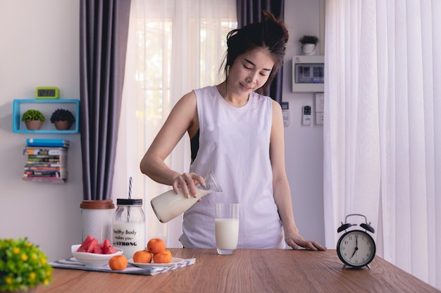 Mesa de madera con joven asiática vertiendo leche