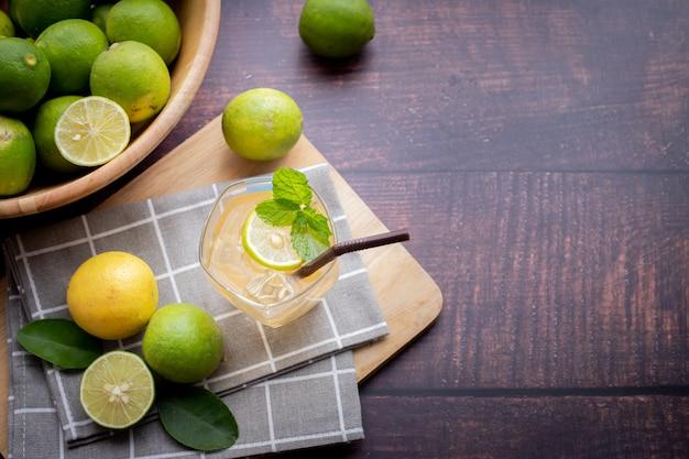 Mesa de madera con jugo de limón recién exprimido con menta y limón en rodajas.