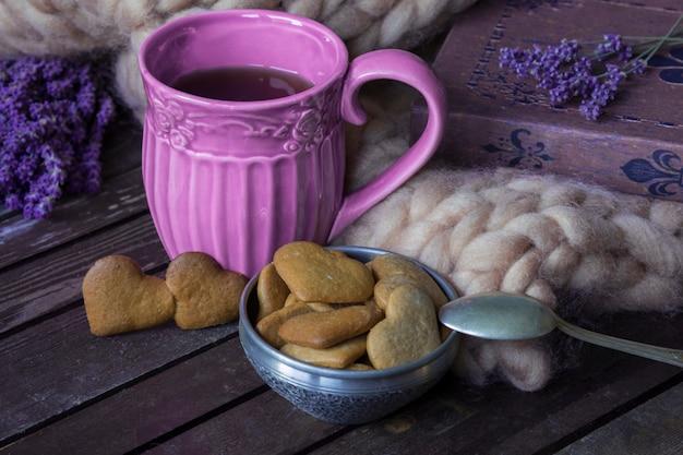 En una mesa de madera, lavanda, plaid, libro, taza de té púrpura, guirnalda y galletas.