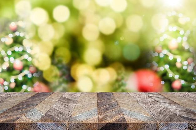 Mesa de madera marrón oscuro vacía con desenfoque abstracto árbol de navidad decoración roja bola y nieve caída