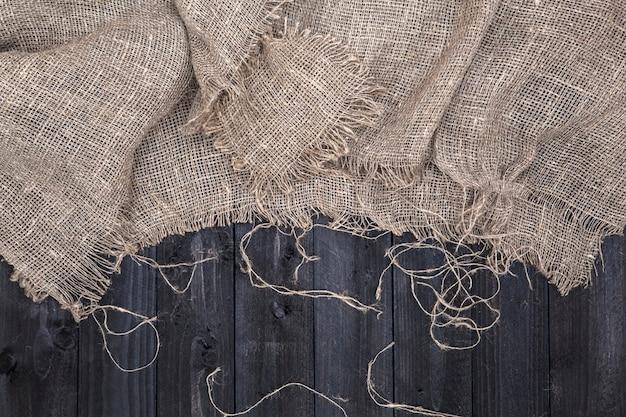 Mesa de madera negra con mantel de arpillera