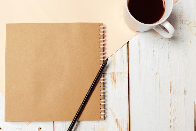 Mesa de madera de oficina con bloc de notas en blanco, lápiz.