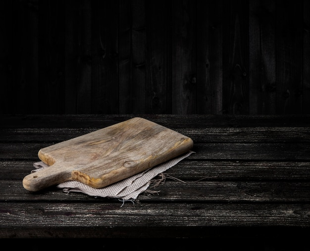 Mesa de madera oscura con tabla de cortar.
