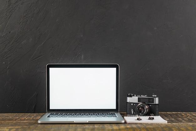 Mesa de madera con pantalla de ordenador portátil en blanco y cámara de fotos retro sobre fondo negro