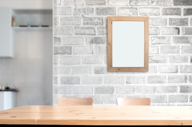 Mesa de madera con pared de ladrillo blanco y marco de fotos.