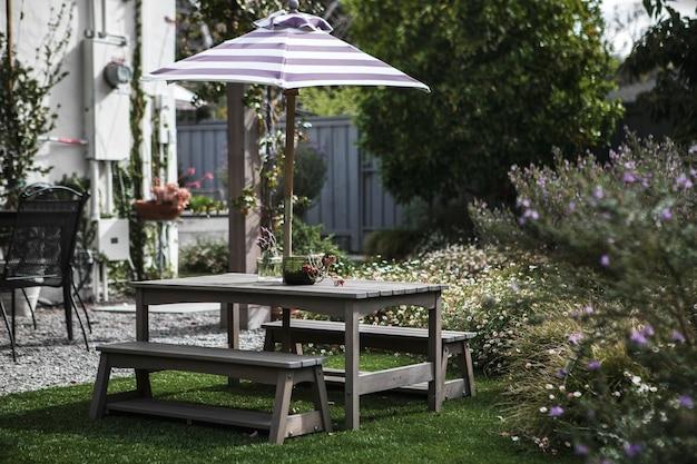 Mesa de madera en un patio con sombrilla