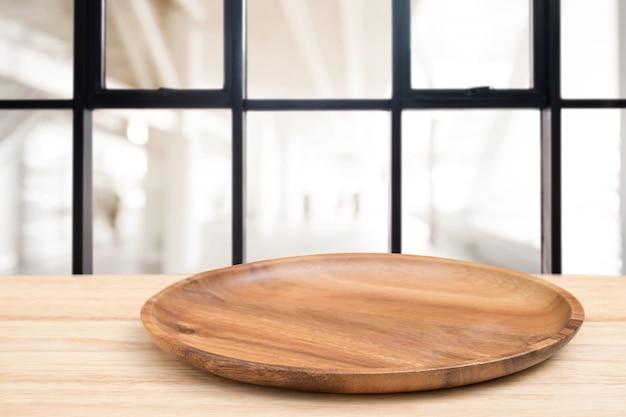 Mesa de madera en perspectiva y bandeja de madera en la parte superior sobre fondo de cafetería desenfoque